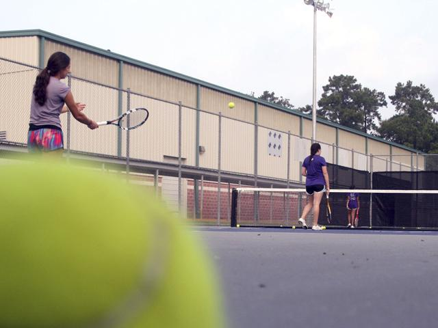Coach Meaghan Ocanas serves to her students at tennis practice