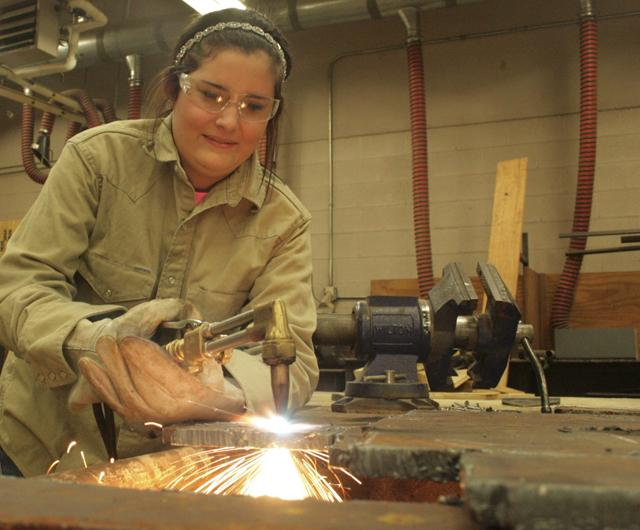 Ag Mechanics Sr Sara Schooley cuts a steel plate with hesitence.