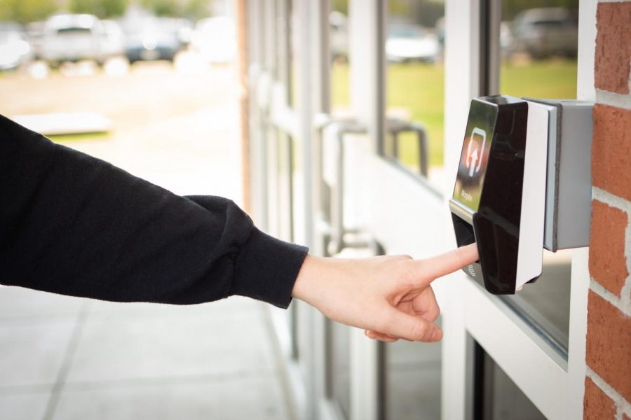 Sophomore Briley Bowers demonstrates how people will use their fingerprints to enter one of five entrances to Lufkin High School. (Photo by DESTINY WEEKS/Lufkin High School Panther Growls)