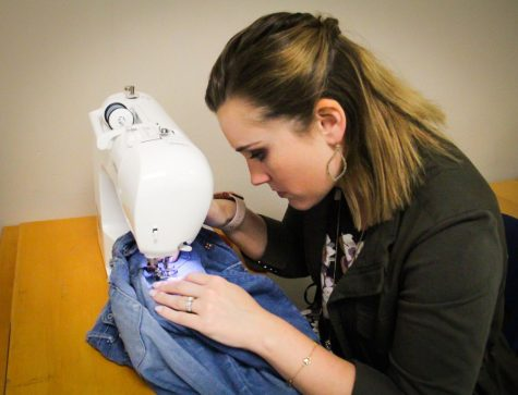 Fashion Design teacher Katie Pruitt works to patch holes in a student