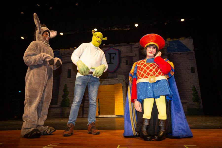 Tolu O'jori (as Donkey), Graham Childers (as Shrek) and Alex Hill rehearse a scene for