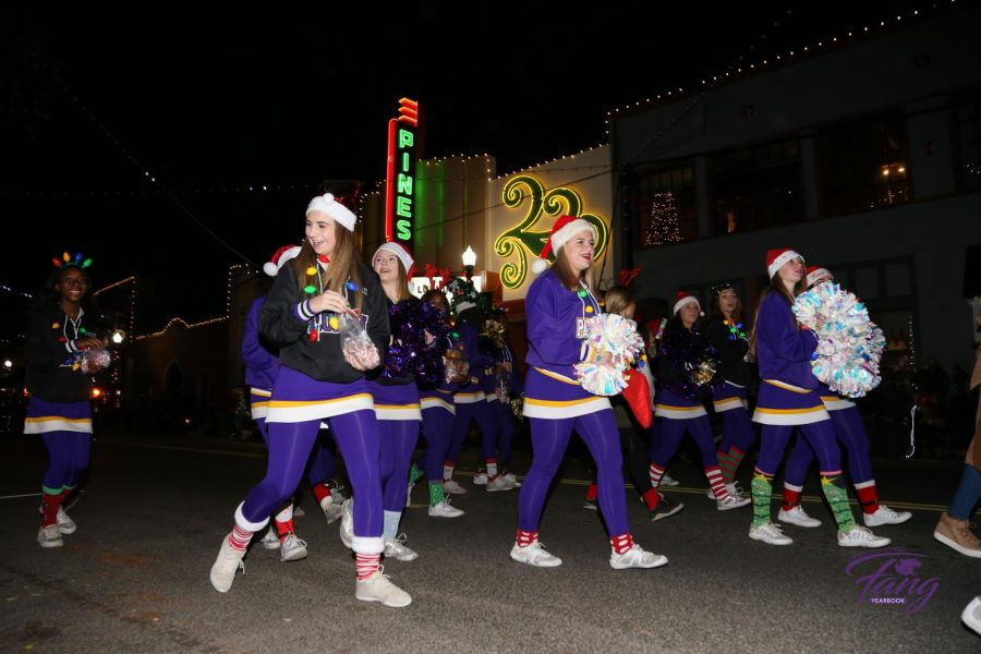 Lufkin High School cheerleaders walk in front of the Pines Theater during the City of Lufkin Downtown Christmas Parade on Monday night. (Photo by ANDY ADAMS/Lufkin ISD)
