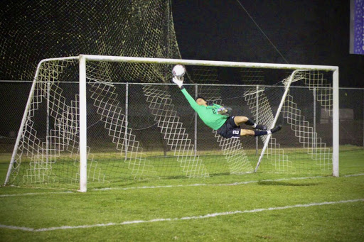 Senior Jose Jaime dives for a ball while practicing during halftime of a Lufkin soccer match. (Photo by VICTOR LEAL/Lufkin. High School Student Media)